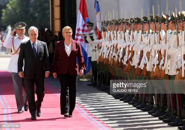 TOPSHOT Chile's President Sebastian Pinera and Croatia's President Kolinda GrabarKitarovic review an honour guard during her welcoming ceremony at La...