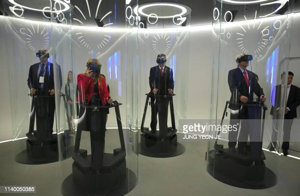 Chile's President Sebastian Pinera tests a virutal reality device as he visits an experience centre operated by SK Telecom in Seoul on April 29 2019...