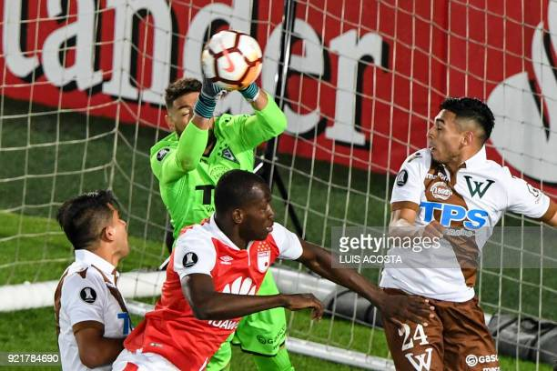Chile's Santiago Wanderers goalkeeper Mauricio Viana stops a ball between Colombia's Independiente Santa Fe midfielder Baldomero Perlaza Chile's...