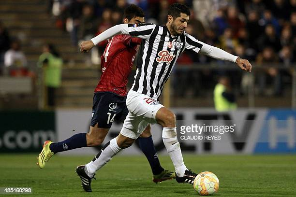 Chile's Universidad Catolica's player Davis Llanos vies for the ball with Paraguay's Libertad's player Pedro Benitez during their Copa Sudamericana...