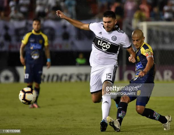 Chile's Universidad de Concepcion player Uruguayan Alexis Rolin vies for the ball with Paraguay's Olimpia player Jorge Ortega during a Copa...