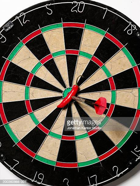 Chili peper and dart on bulls eye of dart board