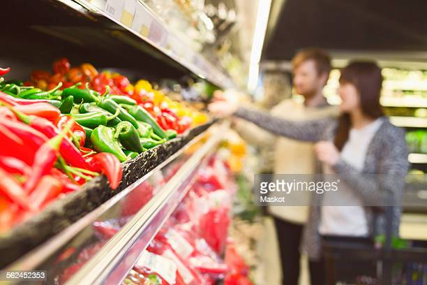 Chili peppers arranged in shelf with couple shopping in background at supermarket