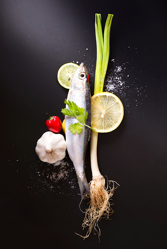 Chilled fresh uncooked sardines with herbs and lemon slice on black moody background. - gettyimageskorea
