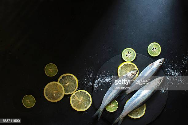 Chilled fresh uncooked sardines with herbs and lemon slice on black moody background.