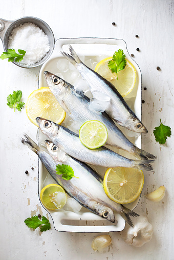 Chilled fresh uncooked sardines with herbs and lemon slice on white background. - gettyimageskorea
