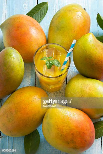 Chilled mango fruit juice in glass with mango.
