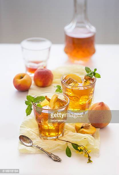 Chilled peach tea in glass with fresh cut peaches on white background.
