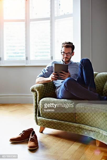 chilling on the sofa with his tablet - alleen één man stockfoto's en -beelden