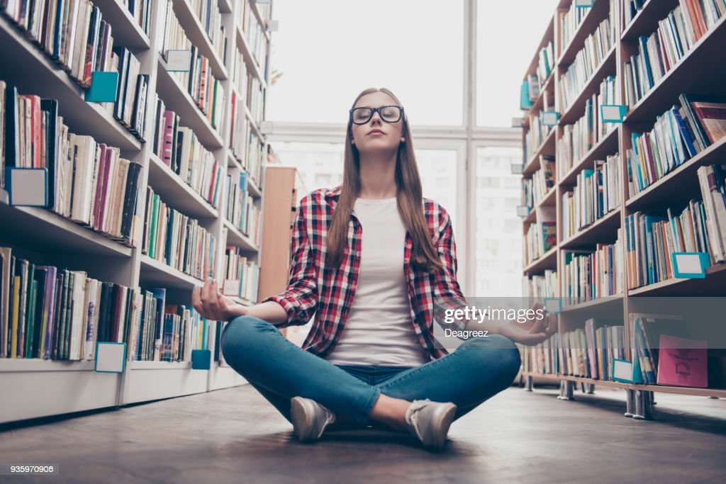 Chilling, wellbeing, vitality, peace, wisdom, education, campus lifestyle. Low angle shot of young calm nerdy girl, practicing yoga in the lotus position on floor in archive room of library : Stock Photo