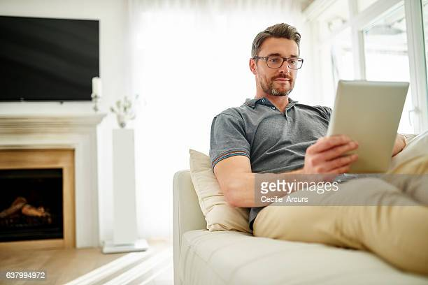 chilling with his tablet - only mature men stock pictures, royalty-free photos & images