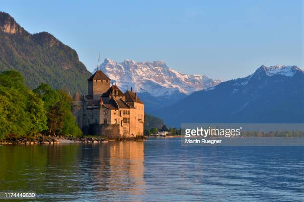 chillon castle (chateau de chillon) located on lake geneva at sunset with the mountain dents du midi in background, clear blue sky. chillon castle, montreux, lake geneva, canton of vaud, dents du midi, switzerland. - montreux stock pictures, royalty-free photos & images