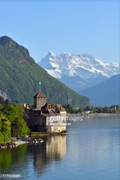 chillon castle (chateau de chillon) located on lake geneva with the mountain dents du midi in background, clear blue sky. chillon castle, montreux, lake geneva, canton of vaud, dents du midi, switzerland. - montreux stock pictures, royalty-free photos & images