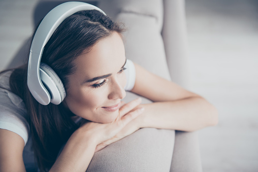 Chillout, satisfaction, therapy, wellness, leisure, lifestyle mode. Charmed adorable brown haired adorable model enjoying to the stereo sound in big modern ear phones in a room, nice break, good-day 929993204