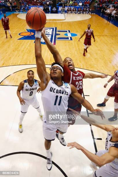 Chima Moneke of the UC Davis Aggies drives to the basket against Kyle Benton of the North Carolina Central Eagles in the first half during the First...