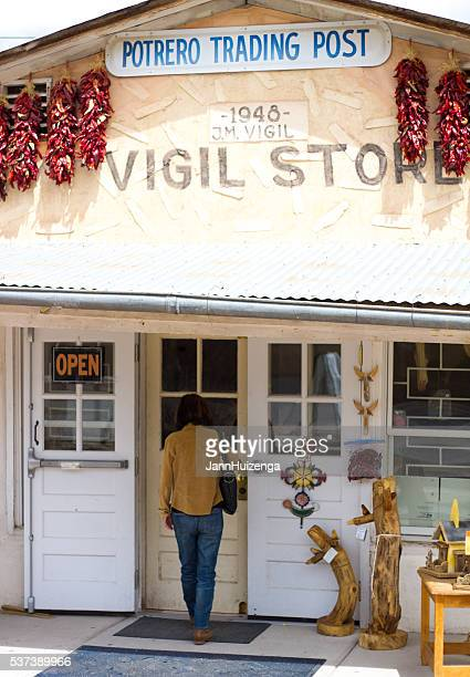 chimayo, nm: handicraft shop with chili pepper ristras outside - trading_post stock pictures, royalty-free photos & images