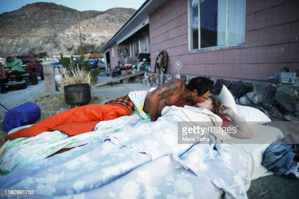Chimene Jackson kisses her husband Johnnie shortly after dawn outside her parents' home which has been deemed uninhabitable due to structural damage...