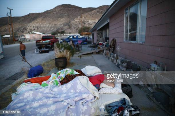 Chimene Jackson sleeps shortly after dawn outside her parents' home which has been deemed uninhabitable due to structural damage from the recent 71...