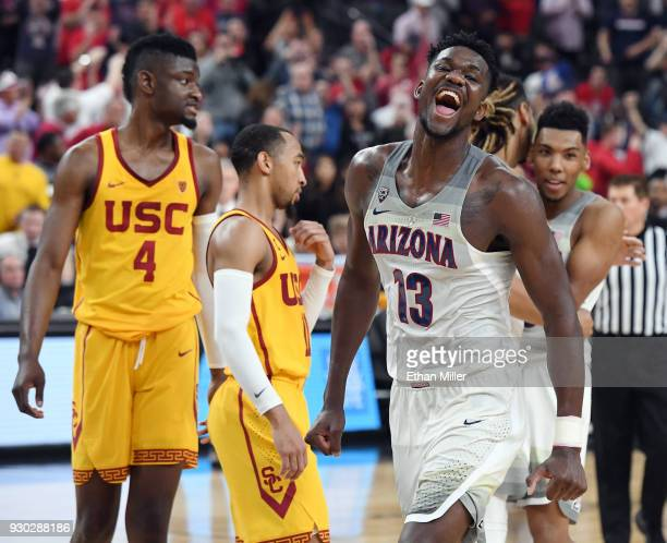 Chimezie Metu and Jordan McLaughlin of the USC Trojans look on as Deandre Ayton of the Arizona Wildcats celebrates after the Wildcats defeated the...