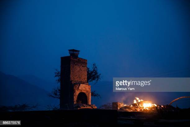 A chimney is all that stands after a fire burned down a home as a brush fire continues to threaten other homes on December 5 2017 in Ventura...