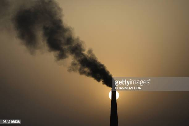 TOPSHOT A chimney of a brick factory emits smoke during sunset in Jalandhar on May 31 2018
