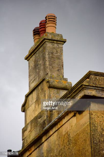 chimney on a tiled roof in the cotswolds - stone house stock pictures, royalty-free photos & images