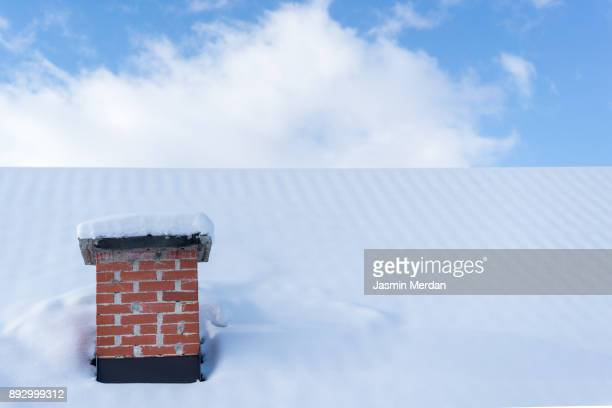 Chimney roof house under winter snow