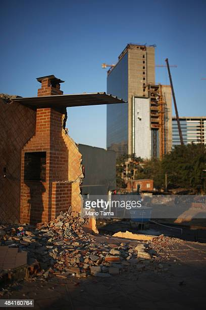 A chimney stands at a partially demolished home in the Vila Autodromo 'favela' community with Olympic Park construction rising in the background on...