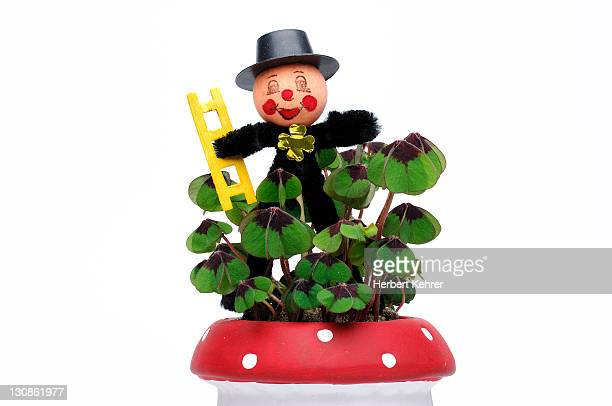 Chimney sweep as a good luck charm with clovers in a flower pot