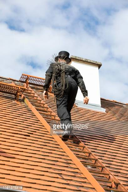 chimney sweep climbing up house roof - schornsteinfeger stock-fotos und bilder