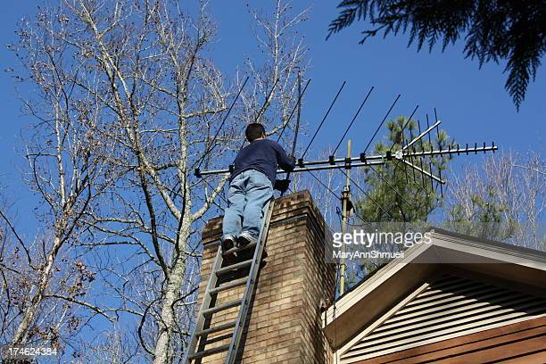 Chimney sweep working on a ladder