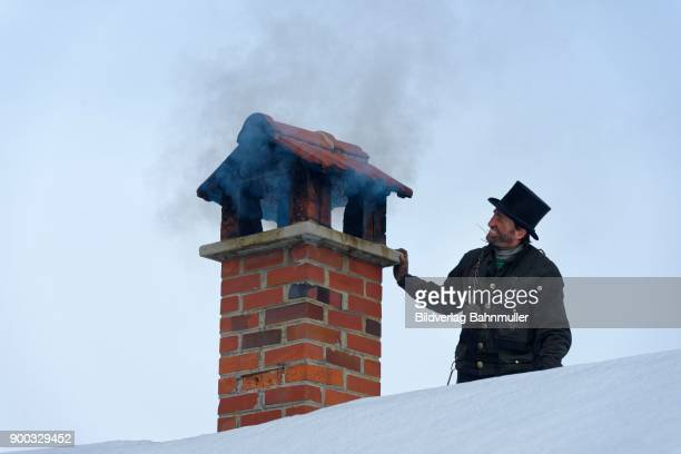 chimney sweeper in winter on a roof with smoky chimney, upper bavaria, bavaria, germany - すす ストックフォトと画像