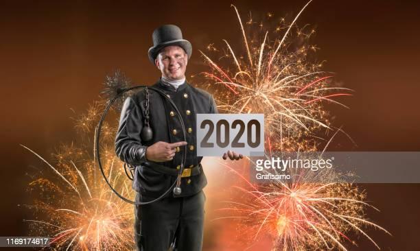 schornsteinfeger mit plakattafel im neuen jahr 2020 stehend im feuerwerk - schornsteinfeger stock-fotos und bilder