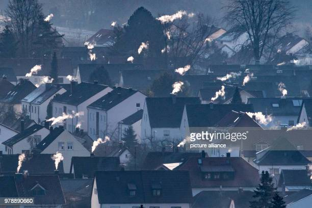 Chimneys billowing smoke from the rooftops of buildings in Straubing Bavaria 28 February 2018 Photo Armin Weigel/dpa