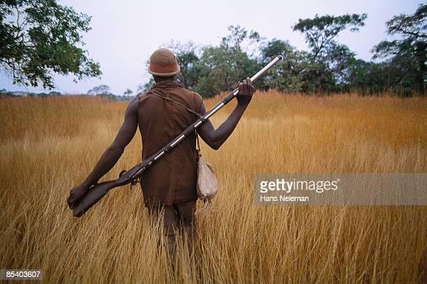 Chimpanzee hunter with rifle slung across his back