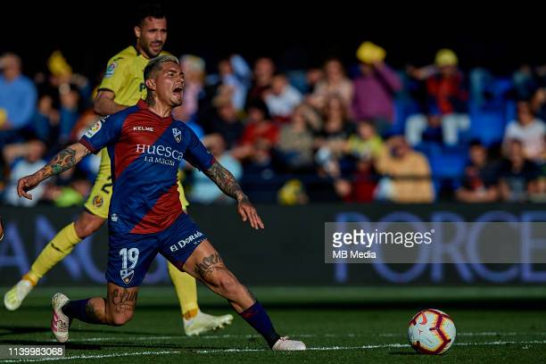 Chimy Avila of SD Huesca competes for the ball with Alvaro of Villarreal CF during the La Liga match between Villarreal CF and SD Huesca at Estadio...