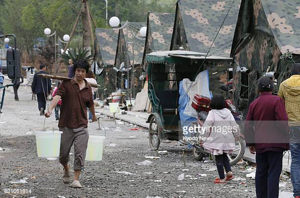 YA'AN China A person carrying water walks past makeshift tents in Lushan county in Ya'an in the southwestern Chinese province of Sichuan on April 21...