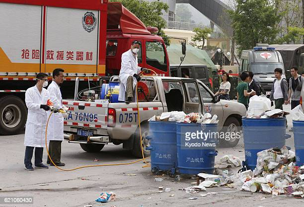 YA'AN China A public sanitation official sprays disinfectant on trash cans in central Lushan county in Ya'an in the southwestern Chinese province of...