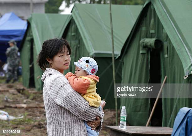 YA'AN China A woman holds a baby near their tent in the Lushan county area of Ya'an in the southwestern Chinese province of Sichuan on April 22...