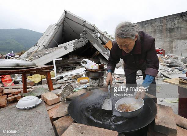 YA'AN China A woman prepares a meal near her collapsed home in the Lushan county area of Ya'an in the southwestern Chinese province of Sichuan on...