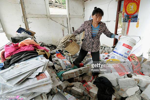 YA'AN China A woman take properties from her damaged home in the Lushan county area of Ya'an in the southwestern Chinese province of Sichuan on April...