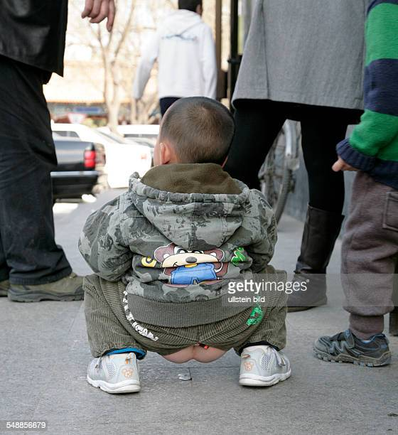 China Beijing Beijing boy is doing his business on the pavement the trousers of the little children have open crotch They do not wear any underwear