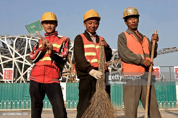 China, Beijing, Chinese worker standing in front of construction site, smiling