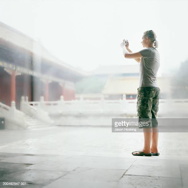China, Beijing, Forbidden City, tourist taking photograph
