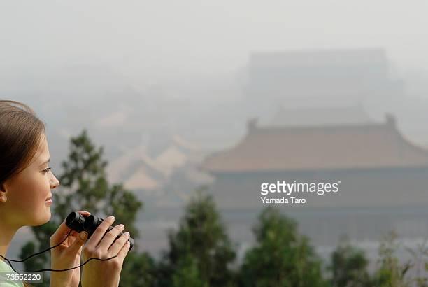 China, Beijing, Forbidden City, young woman with binoculars