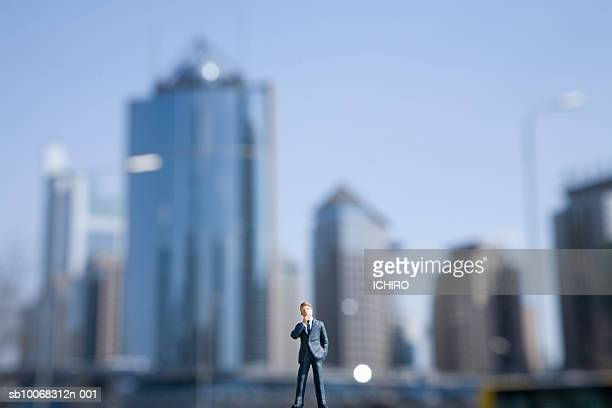 China, Beijing, miniature figure businessman with skyline in background