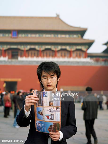 China, Beijing, Palace Museum, tourist with map in front of Forbidden City