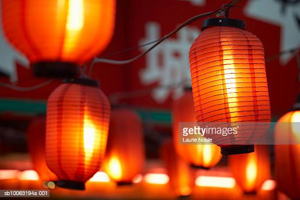 China, Beijing, paper lanterns hanging outdoors at night, close-up