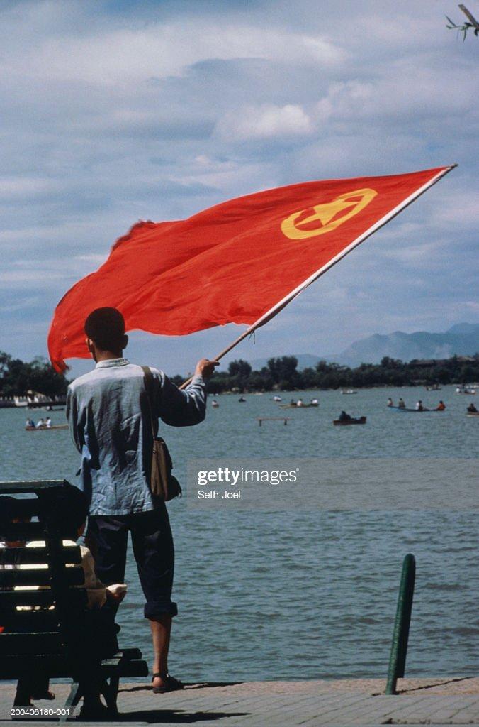China, Beijing, Summer Palace, man waving flag, rear view : Stock Photo
