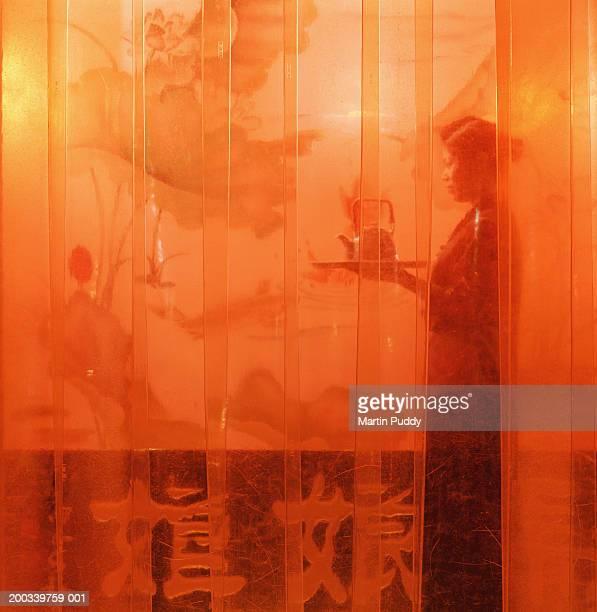 China, Beijing, waitress holding tray and tea pot in tea house